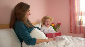 La fille adorable d'enfant apportent le boîte-cadeau actuel à sa mère dans des pyjamas banque de vidéos