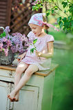 La fille adorable d'enfant dans la robe rose de plaid s'asseyent sur le bureau de vintage avec des lilas dans le panier Photos libres de droits