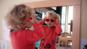 La fille adorable d'enfant a mis les lunettes de soleil rouges sur le miroir proche principal banque de vidéos