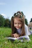 La fille a affiché le livre sur l'herbe Photos stock