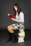 La fille affiche le livre, se reposant sur la pile des livres Photo stock