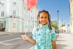 La fille africaine avec le ballon de vol se tient sur la rue Photos stock