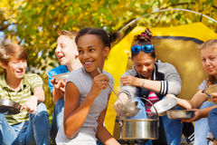La fille africaine fait cuire la soupe dans le pot pour des amis Images libres de droits