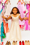 La fille africaine pendant les achats se tient parmi des robes Photographie stock libre de droits