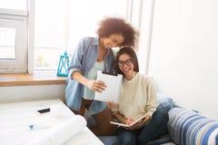 La fille afro-américaine est proche debout son ami et comprimé d'apparence à elle La fille avec de longs cheveux s'assied sur le  Photos stock