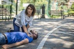 La fille aide un type inconscient après accident Image libre de droits