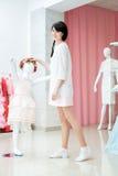 La fille ajuste la robe sur le mannequin Photo libre de droits