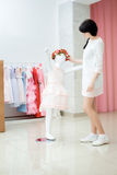 La fille ajuste la robe sur le mannequin Photos libres de droits