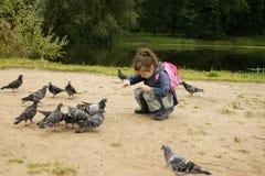 La fille alimente des pigeons Photo libre de droits