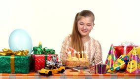 La fille allume des bougies sur son gâteau d'anniversaire table clips vidéos