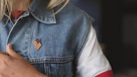 La fille américaine blonde met une goupille sur sa veste banque de vidéos