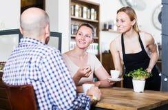La fille amicale de serveur a apporté la tasse de café pour des couples de differe photographie stock libre de droits