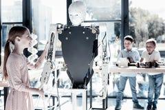 La fille amicale serrant la main à l'humain aiment le robot Photographie stock libre de droits