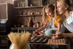 La fille amusée mettant la pâtisserie dans la cuisson sonne Photo stock