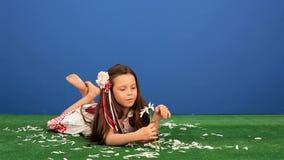 La fille 6 années se trouvant sur l'herbe et sépare banque de vidéos
