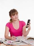 La fille appelle une annonce dans le gazate Photographie stock libre de droits