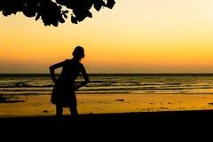 La fille apprécie la liberté à la plage de coucher du soleil Images libres de droits