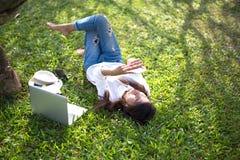 La fille apprécient la musique de écoute et lire un livre et jouent l'ordinateur portable Images libres de droits