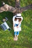 La fille apprécient la musique de écoute et lire un livre et jouent l'ordinateur portable sur le champ d'herbe du parc Photos libres de droits