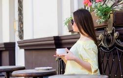 La fille appr?cient le caf? de matin Date de attente La femme dans des lunettes de soleil boivent du caf? dehors E photographie stock
