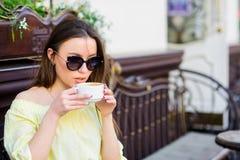 La fille appr?cient le caf? de matin La femme dans des lunettes de soleil boivent du caf? dehors La fille d?tendent dans la tasse photos libres de droits