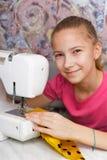 La fille apprend à coudre sur une machine à coudre photographie stock libre de droits