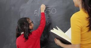 La fille apprend des maths avec le professeur dans la classe banque de vidéos