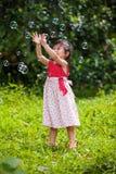 La fille asiatique attrape des bulles de savon sur le fond de nature outdoors Photos stock