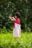 La fille asiatique attrape des bulles de savon sur le fond de nature outdoors Photographie stock