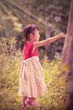 La fille asiatique attrape des bulles de savon sur le fond de nature outdoors Image libre de droits