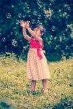 La fille asiatique attrape des bulles de savon sur le fond de nature outdoors Photographie stock libre de droits