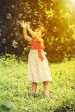 La fille asiatique attrape des bulles de savon sur le fond de nature outdoors Photos libres de droits