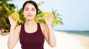 La fille asiatique avec la belle peau claire tient des fruits sur la plage avec le fond de mer - concept de sant? et de perte de  photographie stock