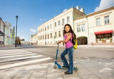 La fille asiatique avec de longs cheveux se tient sur le scooter Photographie stock
