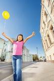 La fille asiatique avec des bras tient le ballon de vol Photo stock