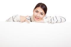 La fille asiatique avec le point d'écharpe vers le bas, reposent son menton sur le signe vide Image stock