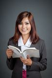 La fille asiatique d'affaires a lu un regard de livre à l'appareil-photo Images stock