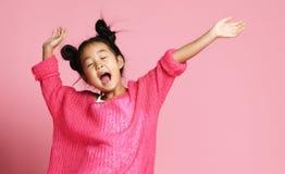 La fille asiatique d'enfant en chandail rose, pantalon blanc et petits pains drôles chante la danse de chant sur le rose photographie stock libre de droits