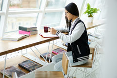 La fille asiatique dans la causerie coworking avec des amis dans les réseaux sociaux par l'intermédiaire du téléphone s'est relié Images libres de droits