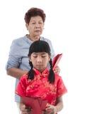 La fille asiatique dans le Chinois rouge habillent soumettre à une contrainte avec sa grand-mère photographie stock