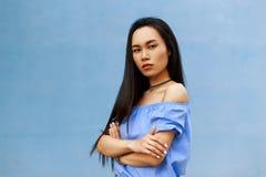 La fille asiatique de belle brune avec de longs cheveux a plié sa main photographie stock libre de droits