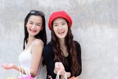 La fille asiatique de portrait de duo a heureux et le sourire avec le colo d'achats image libre de droits