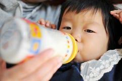 La fille asiatique est lait de consommation images libres de droits