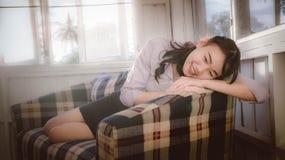 La fille asiatique est souriante et situante dans le divan, se trouvant sur le sofa Photo stock