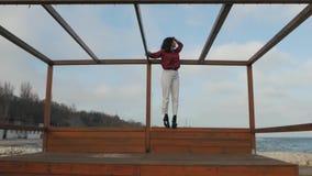 La fille asiatique examine la distance avec une structure en bois banque de vidéos