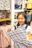 La fille asiatique heureuse choisit des vêtements dans le magasin de mail ou d'habillement, s photos libres de droits