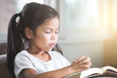 La fille asiatique mignonne de petit enfant a fermé ses yeux et a plié sa main image stock