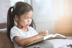 La fille asiatique mignonne de petit enfant a fermé ses yeux et a plié sa main photo stock