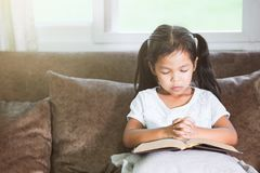 La fille asiatique mignonne de petit enfant a fermé ses yeux et a plié sa main photographie stock