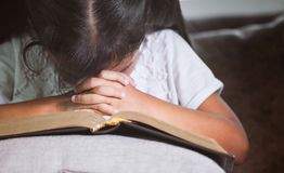 La fille asiatique mignonne de petit enfant a fermé ses yeux et a plié sa main images stock